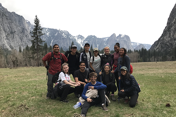 Group of students on a meadow with mountains behind them