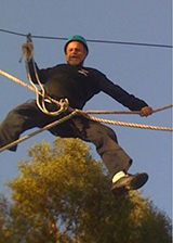A man participates in the High Ropes Challenge Course.